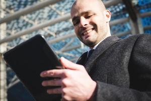 erfolgreicher eleganter modischer Geschäftsmann mit Tablette foto