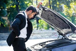 Mann, der in der Nähe eines kaputten Autos steht foto
