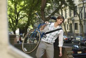 Geschäftsmann, der Fahrrad im Freien trägt foto