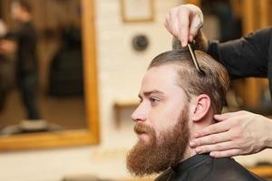 fröhlicher männlicher Friseur dient seinem Klienten foto