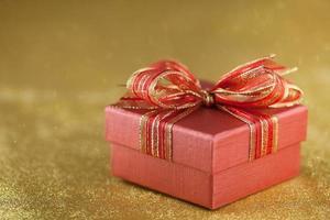 rote Geschenkbox auf glitzerndem Goldhintergrund