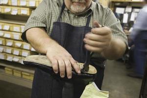 Mittelteil des Mannes, der in der Schuhmacherwerkstatt arbeitet foto