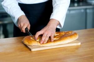 männlicher Koch, der Brotlaib schneidet foto
