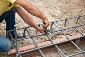 Arbeiter bereiten Stahlmasten für den Hausbau vor foto