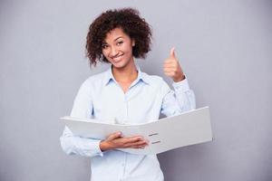 Geschäftsfrau hält Ordner und zeigt Daumen nach oben foto