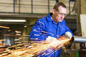 Stahlbauarbeiter schleifen Metall mit Winkelschleifer foto