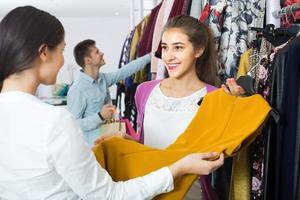 Berater, der Kunden Herbstkleidung im Laden anbietet foto