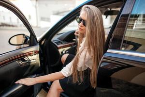 Geschäftsfrau in der weißen Bluse, die in einem Auto sitzt foto