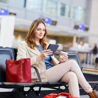 Frau am internationalen Flughafen, E-Book lesen und Kaffee trinken foto