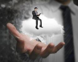 männliche Hand zeigt Geschäftsmann, der auf weißer Wolke sitzt foto