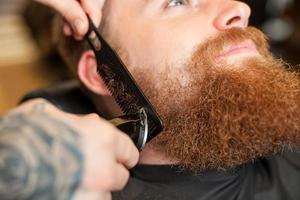 geschickter männlicher Friseur bedient seinen Kunden foto