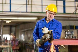 Stahlbauarbeiter schneiden Metall mit Winkelschleifer foto