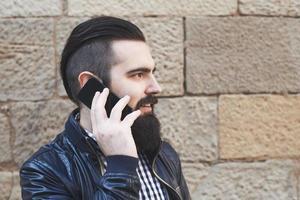 attraktiver bärtiger Mann, der am Telefon spricht foto