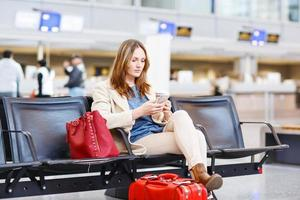 Frau am internationalen Flughafen wartet auf Flug am Terminal foto