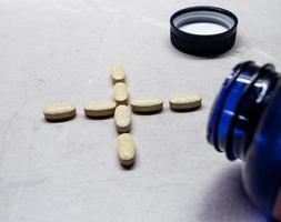 Vitamin- und Mineralstoffpillen / -tabletten in einem Plus- / Positivsymbol foto