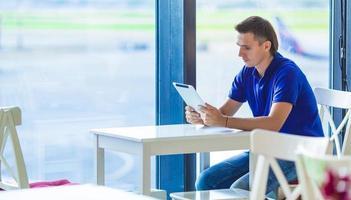 junger Mann am Flughafencafé beim Warten auf das Einsteigen foto