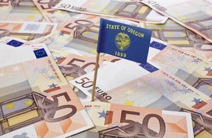 Flagge von Oregon, die in 50-Euro-Banknoten steckt. (Serie) foto