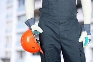 Arbeiter auf einer Baustelle hält einen Helm foto