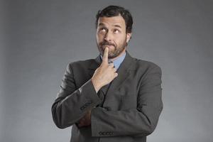 kontemplativer Geschäftsmann, der gegen grauen Hintergrund steht foto