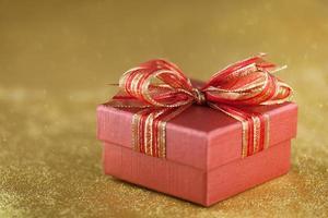 rote Geschenkbox auf glitzerndem Goldhintergrund foto