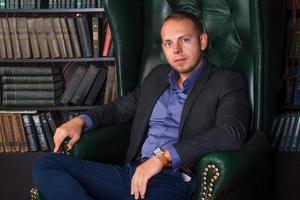 der Mann, ruhiger und selbstbewusster Geschäftsmann, der auf einem Stuhl sitzt