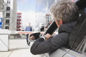Hamburg, Geschäftsmann, der im Auto vor geschlossener Barriere sitzt foto