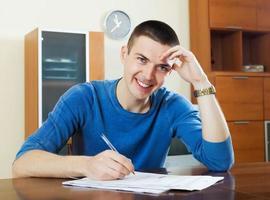 glücklicher Mann füllt Fragebogen aus foto