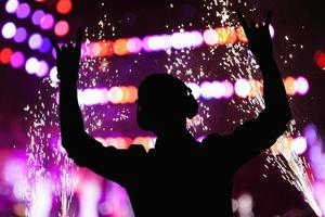 Silhouette von DJ, der in einem Nachtclub auftritt foto