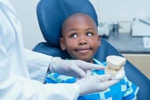 abgeschnittener Zahnarzt, der Jungenprothesenzähne zeigt foto