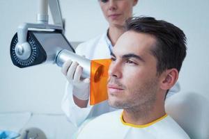 ernsthafter junger Mann, der sich einer zahnärztlichen Untersuchung unterzieht foto