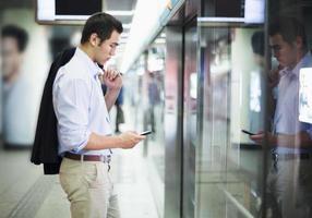 Geschäftsmann, der auf sein Telefon schaut und auf U-Bahn wartet foto