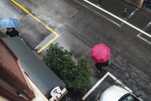 Person mit rotem Regenschirm über eine Straße