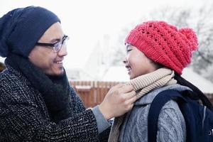 Vater repariert den Schal der Tochter foto