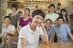 junge Frau mit Gruppe von Freunden in einem Café