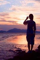 Frau, die am Strand steht und einen Cheongsam trägt foto