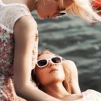 zwei schöne Mädchen am See Pier
