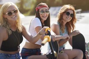 Drei Mädchen ruhen sich im Skatepark aus foto
