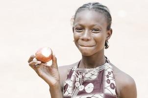 Wunderschönes afrikanisches schwarzes Schulmädchen beißt einen Apfel - Gesundheitshintergrund foto