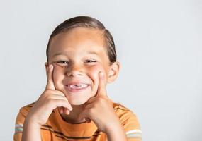 Junge zeigt fehlende Zähne.