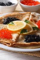 dünne Pfannkuchen mit roter und schwarzer Kaviar-Nahaufnahme, vertikal
