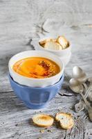 Kürbissuppe in Keramikschalen auf einem hellen hölzernen Hintergrund foto