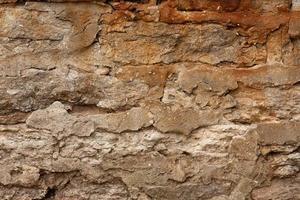 braune und neutrale Steinmauer Hintergrundbeschaffenheit foto