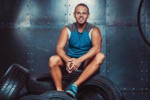 Sportler sitzt auf der Reifenmaschine. Konzept von Fitnessstudio, Gesundheit foto