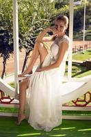 schöne lächelnde Braut im eleganten Hochzeitskleid, das im Garten aufwirft