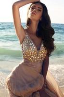 Mädchen mit dunklem Haar im luxuriösen Kleid, das am Strand aufwirft