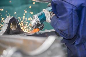 Arbeiter poliert einen Teil der Stahlkonstruktion. foto