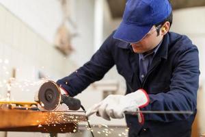 Arbeiter schleift eine Metallplatte