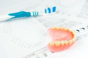 Zahnersatz, Zahnbürste für Zahnausrüstung, Zahnpasta-Isolat auf weißem Hintergrund foto