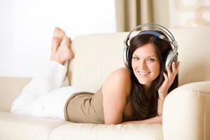 glückliche Frau mit Kopfhörern, die auf Sofa in der Lounge liegen foto