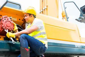 asiatischer Mechaniker, der Baufahrzeug repariert foto